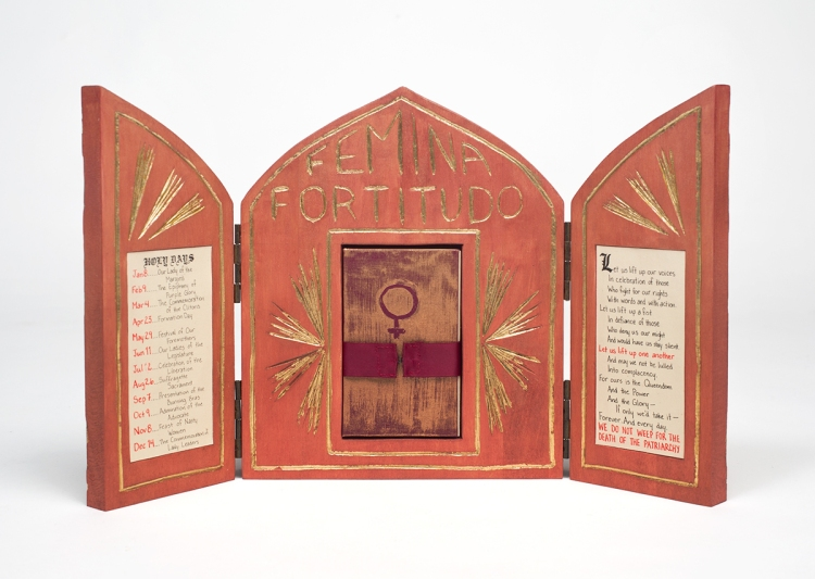 Photo of open altar standing on table - inlaid paper on left and right inside doors - nestled book with Venus symbol is held in place by a burgundy ribbon