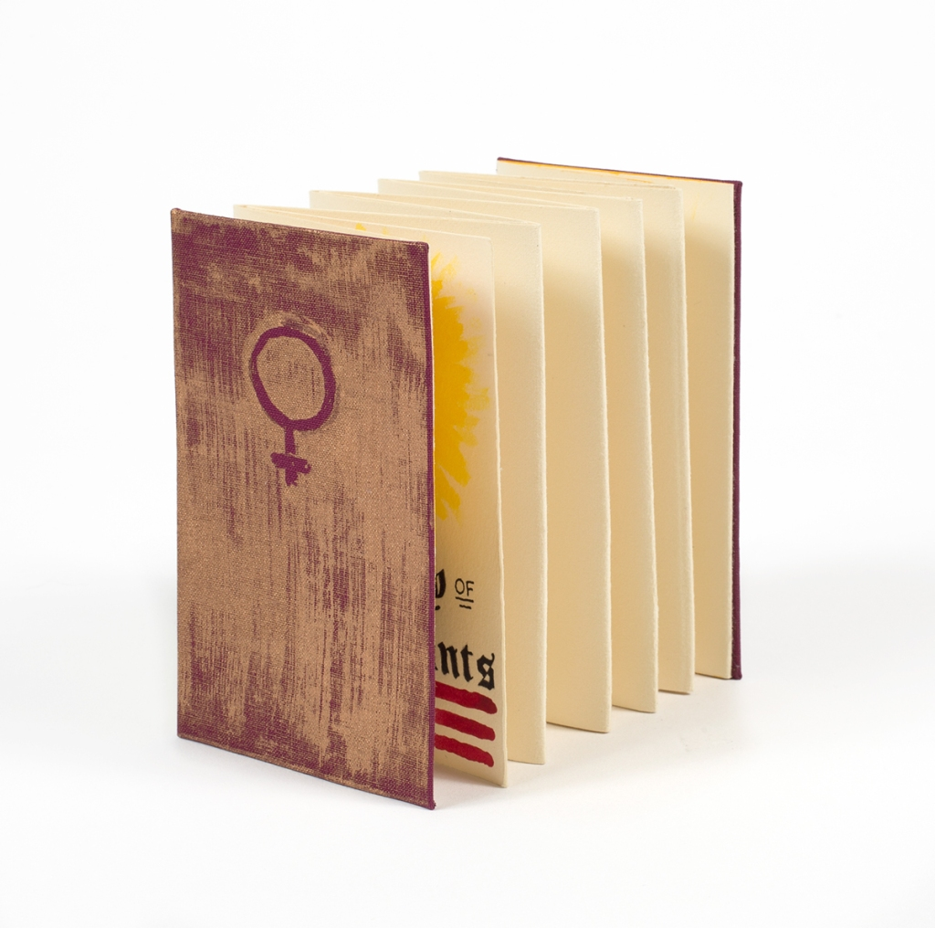 Photo of book alone standing on table showing accordion structure with front cover visible - Venus symbol and gold rough brushed detail