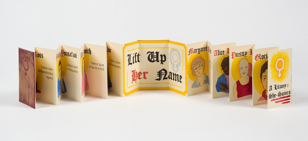 """Photo of accordion book stretched open standing on table - center 3 pages read """"Lift Up Her Name"""" in calligraphy - pages to left and right show ink illustrations of faces with names in calligraphy above"""