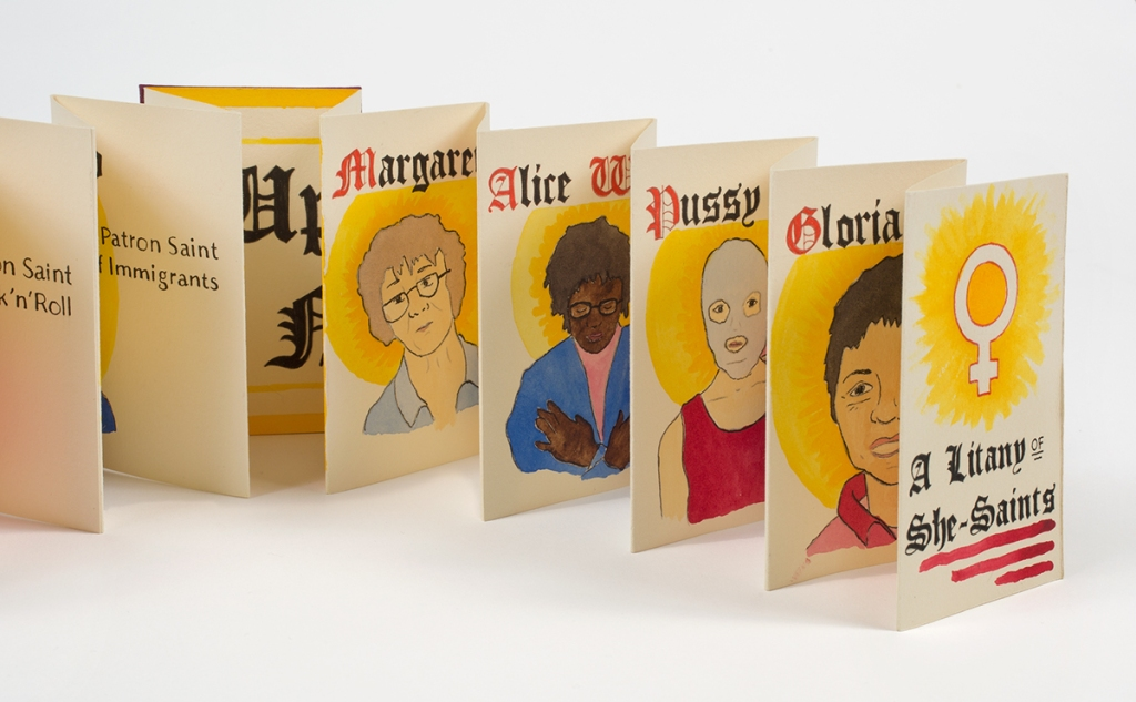 Photo of pages from accordion book standing open on table - partially visible illustrations and names: Margaret Crane, Alice Walker, Pussy Riot, Gloria Andzaldua
