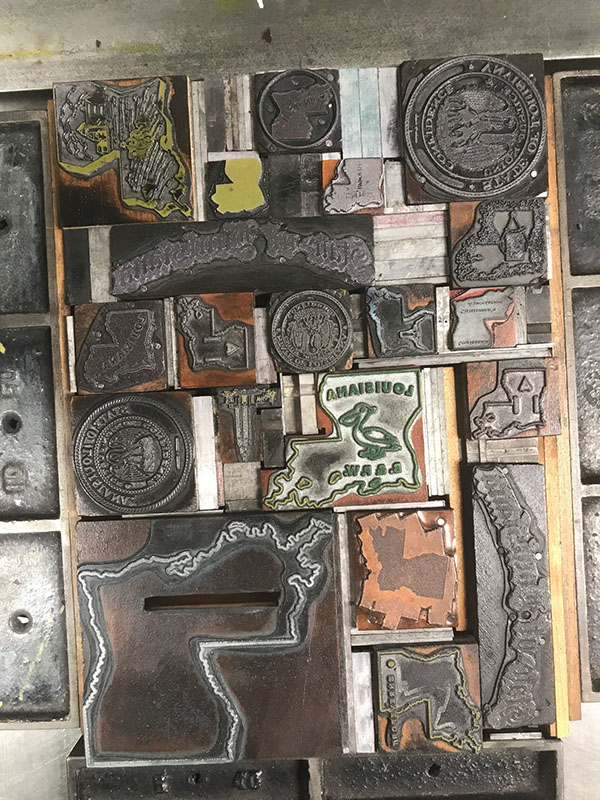 Photo of letterpress bed with dozens of Louisiana die cuts of various sizes and letterpress furniture