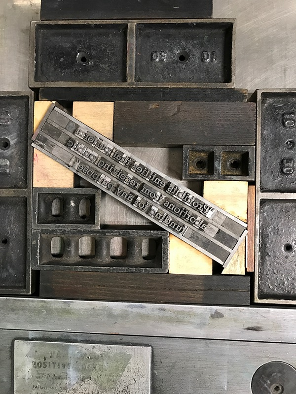 Photo of letterpress bed with small text set at an angle and letterpress furniture